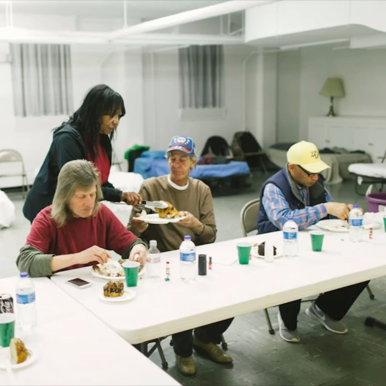 People eating in a shelter.